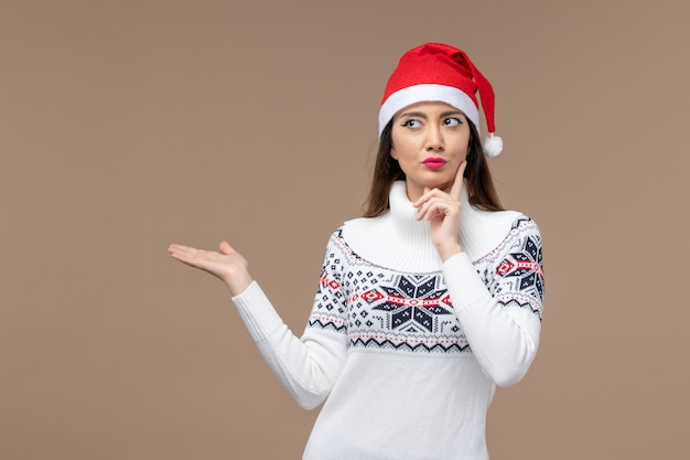 Front view young woman with thinking expression on brown background holiday emotion christmas