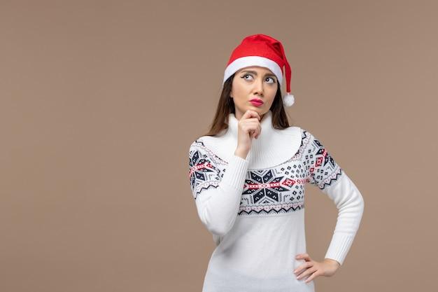 Giovane donna di vista frontale con l'espressione di pensiero sul natale marrone di emozione del nuovo anno del fondo