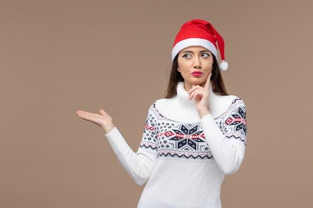 Вид спереди молодая женщина с выражением мышления на коричневом фоне, праздничная эмоция, рождество
