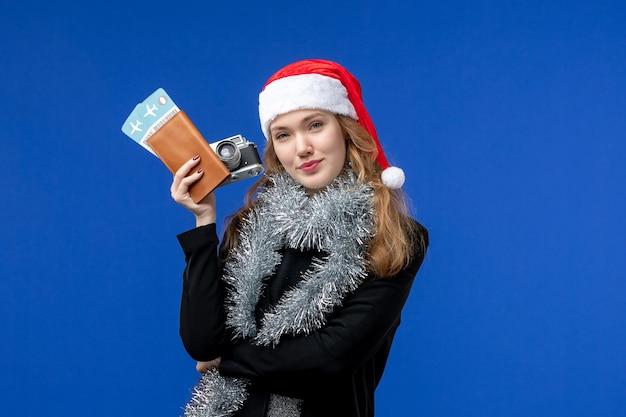Vista frontale della giovane donna con i biglietti e la macchina fotografica sulla parete blu