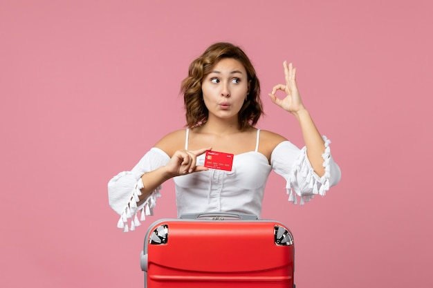 Front view of young woman with vacation bag holding bank card on pink floor trip model vacation color voyage sea