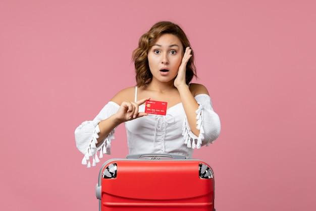 Vista frontale della giovane donna con la borsa per le vacanze che tiene la carta di credito sul pavimento rosa vacanza viaggio modello viaggio mare colore