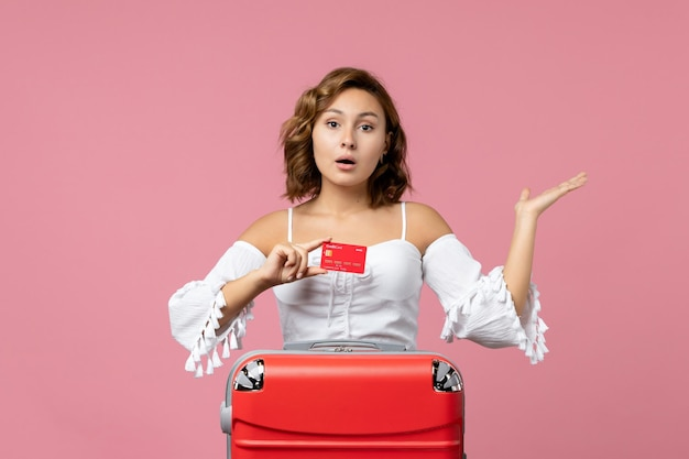 Front view of young woman with vacation bag holding bank card on pink wall
