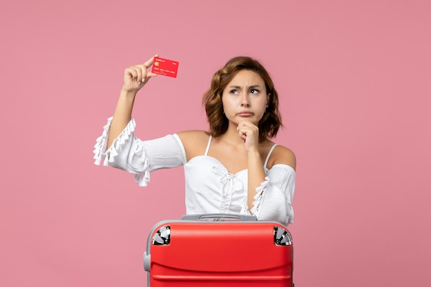 Front view of young woman with vacation bag holding red bank card on pink floor sea model voyage vacation trip color