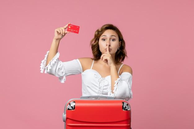 Vista frontale della giovane donna con la borsa delle vacanze che tiene la carta di credito rossa sul muro rosa