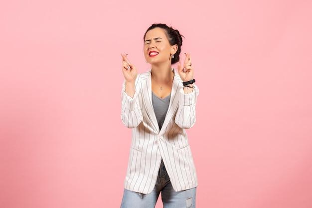 Vista frontale giovane donna con giacca bianca incrociando le dita su sfondo rosa donna moda donna emozioni colore