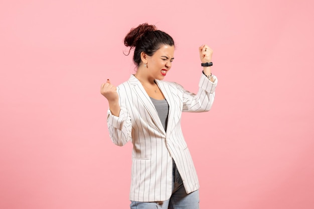 Front view young woman with white jacket emotionally rejoicing on pink background clothing lady emotions color fashion woman