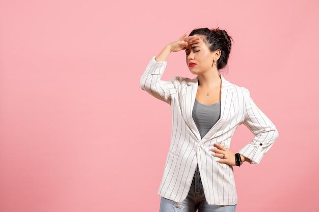 Vista frontale giovane donna con giacca bianca su sfondo rosa emozioni donna moda donna colore sentimento