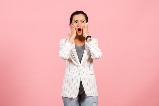 Vista frontale giovane donna con giacca bianca e faccia scioccata su sfondo rosa emozioni donna moda sensazione colore donna