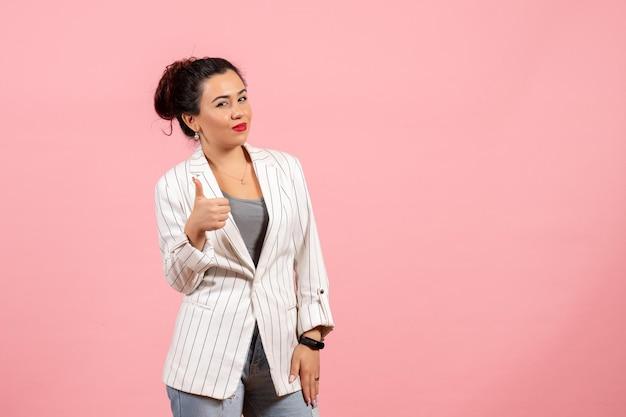 Vista frontale giovane donna con giacca bianca che mostra un segno fantastico su sfondo rosa abbigliamento donna emozioni colore moda donna