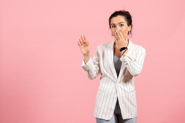 Vista frontale giovane donna con giacca bianca e faccia sorpresa su sfondo rosa abbigliamento donna emozioni colore moda donna