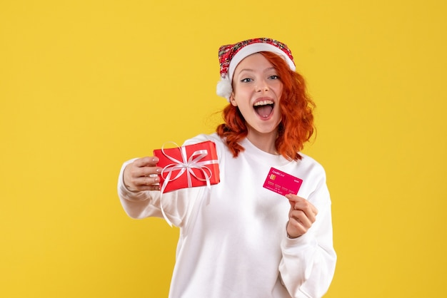 Front view of young woman with xmas present and bank card on yellow wall