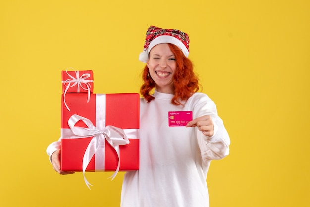 Vista frontale della giovane donna con regali di natale e carta di credito sulla parete gialla