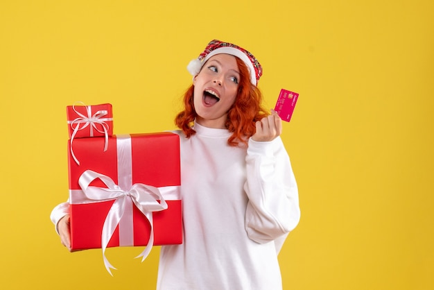 Front view of young woman with xmas presents and bank card on yellow wall