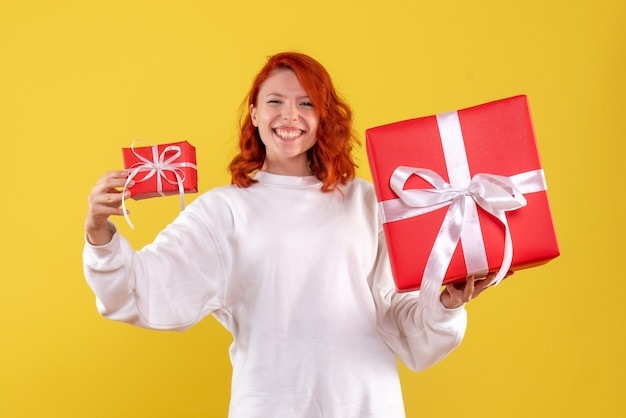 Vista frontale della giovane donna con regali di natale sulla parete gialla