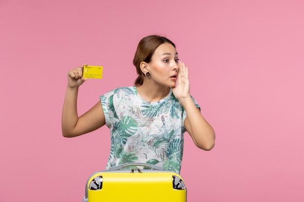 Vista frontale della giovane donna con carta di credito gialla e borsa sul muro rosa