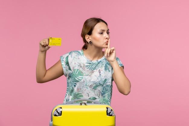 Vista frontale della giovane donna con carta di credito gialla e borsa per le vacanze sulla parete rosa