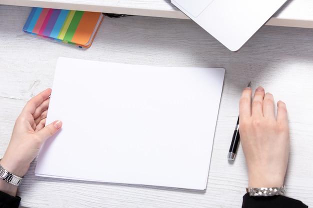 Una giovane donna di vista frontale che lavora con gli spazii in bianco vuoti davanti alla tavola con l'affare di attività di lavoro dei computer portatili