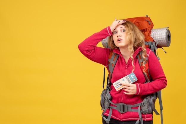 Vista frontale della giovane ragazza in viaggio preoccupata ed emotiva in maschera medica tenendo il biglietto