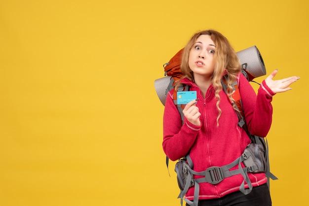 Vista frontale della giovane ragazza in viaggio preoccupata nella mascherina medica che tiene la carta di credito