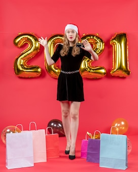 Front view young xmas lady in black dress bags on floor balloons on red