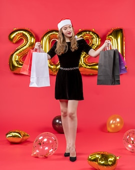 Front view young xmas lady in black dresslooking at shopping bags balloons on red