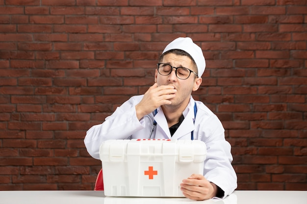 Front view young yawning doctor in white medical suit with first aid kit on brown brick wall