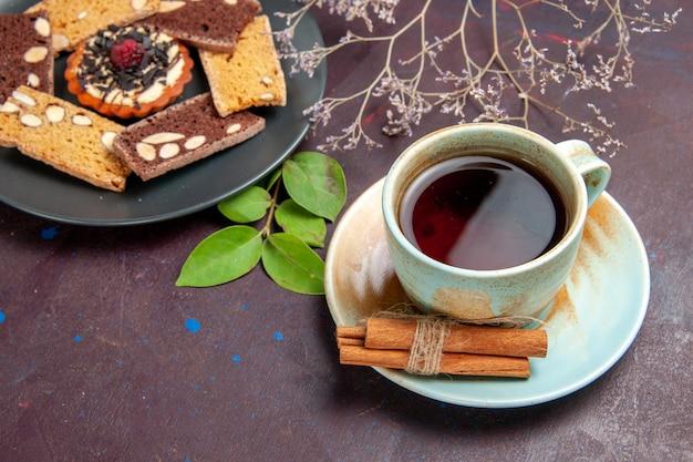 어두운 보라색 공간에 차 한잔과 함께 전면보기 맛있는 케이크 조각