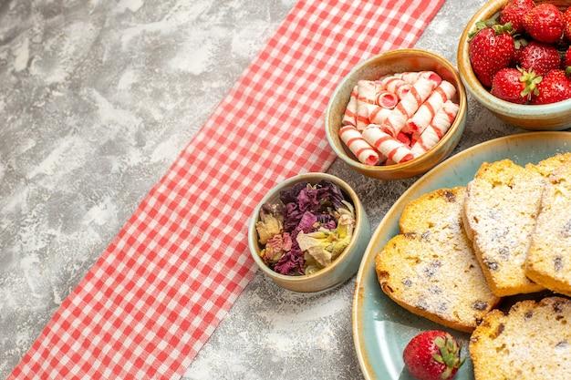 正面図白い表面の甘いパイの果実に新鮮なイチゴとおいしいケーキのスライス