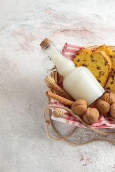 Fette di torta gustosa vista frontale con latte e noci sulla superficie bianca