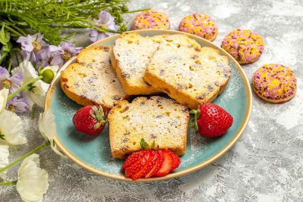 正面図明るい表面のパイの甘いケーキにイチゴとクッキーとおいしいケーキのスライス