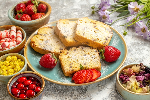 正面図明るい表面の果物の甘いケーキのパイにイチゴとおいしいケーキのスライス