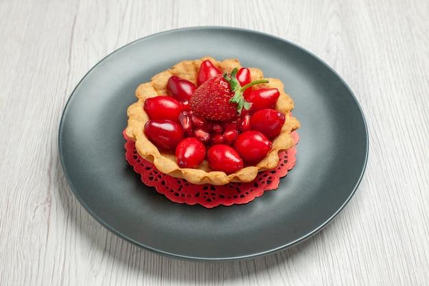 正面図白い机の上の新鮮な果物とおいしいケーキケーキデザートフルーツ赤