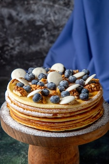 Front view yummy cake with walnuts blueberries and cookies dark surface