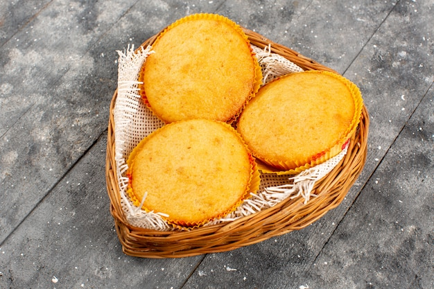 Вид спереди вкусные пирожные, приготовленные коричневой круглой внутренней корзиной на сером полу