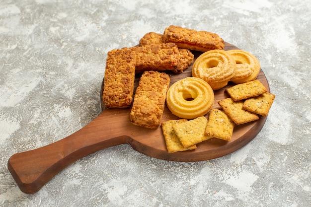 白いテーブルの上のクラッカーとクッキーの正面図おいしいケーキクッキービスケットケーキ
