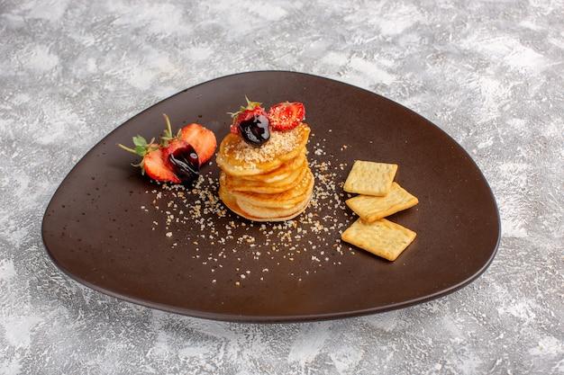 白いテーブルの上のプレートの内部のイチゴで設計された正面おいしいチップ、チップスナックフルーツベリー
