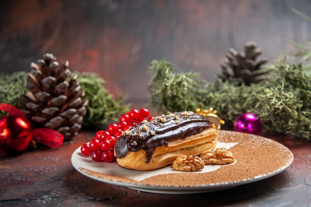 Front view yummy choco eclairs with red berries on dark background