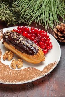 Front view yummy choco eclairs with red berries on dark floor pie cake dessert sweet