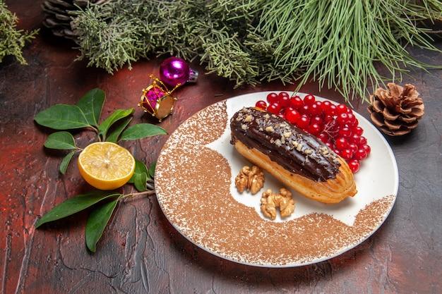 Вкусные шоколадные эклеры с красными ягодами на темном столе, пирог, десерт, сладкий, вид спереди