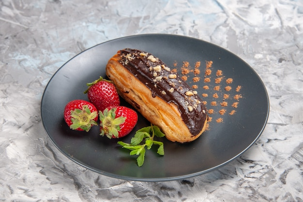 Front view yummy choco eclairs with strawberries on light table dessert cake candy
