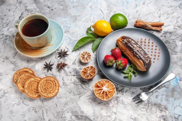 ライトテーブルのデザートケーキビスケットにお茶とフルーツを添えた正面図のおいしいチョコエクレア