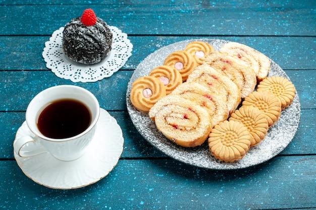 파란색 소박한 책상 차 달콤한 케이크 쿠키 비스킷에 차 롤과 쿠키의 컵과 함께 전면보기 맛있는 초콜릿 공