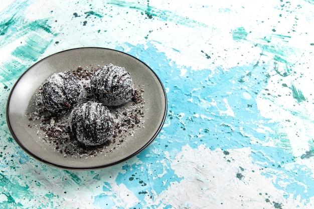 Vista frontale gustose palline di cioccolato torte al cioccolato tonde formate con glassa sulla superficie blu torta cuocere biscotti al cioccolato dolce di zucchero