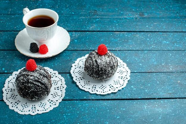 Palline di cioccolato squisite di vista frontale con la tazza di tè sul biscotto rustico blu del biscotto della torta del tè dello scrittorio dolce