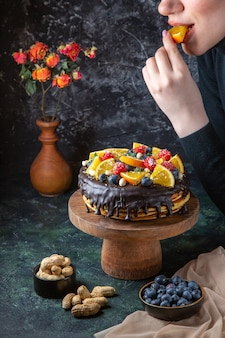 어두운 벽에 여성에 의해 신선한 과일로 장식되는 전면보기 맛있는 초콜릿 케이크