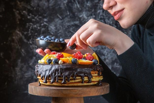 暗い壁に女性によって果物で飾られている正面のおいしいチョコレートケーキ