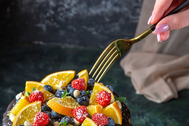 Torta al cioccolato gustosa vista frontale con frutta fresca sulla parete scura