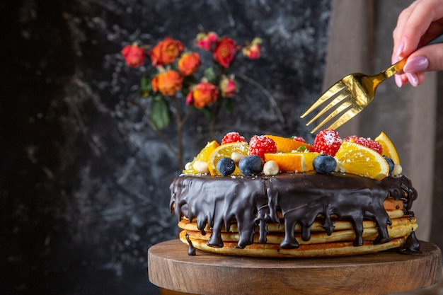 Front view yummy chocolate cake with fresh fruits on dark wall