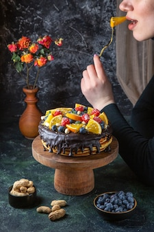 어두운 벽에 여성이 먹는 신선한 과일과 함께 전면보기 맛있는 초콜릿 케이크
